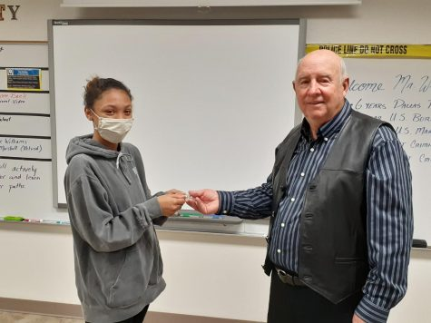 Senior Abinie Prarson handing Dale Williams first responder appreciation coin